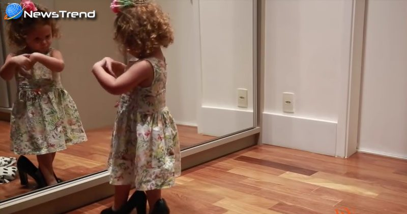 little girld dances in front of the mirror